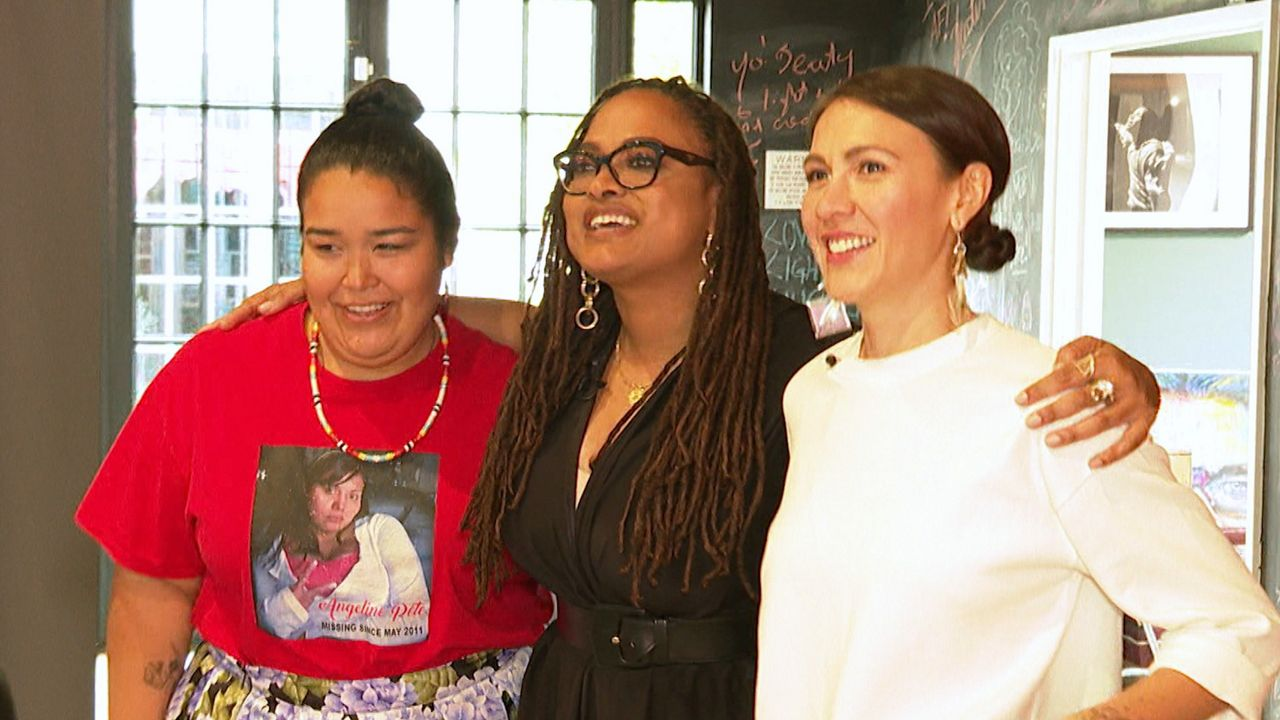 Ava DuVernay puts her arms around the shoulders of two women filmmakers as they smile for the cameras.
