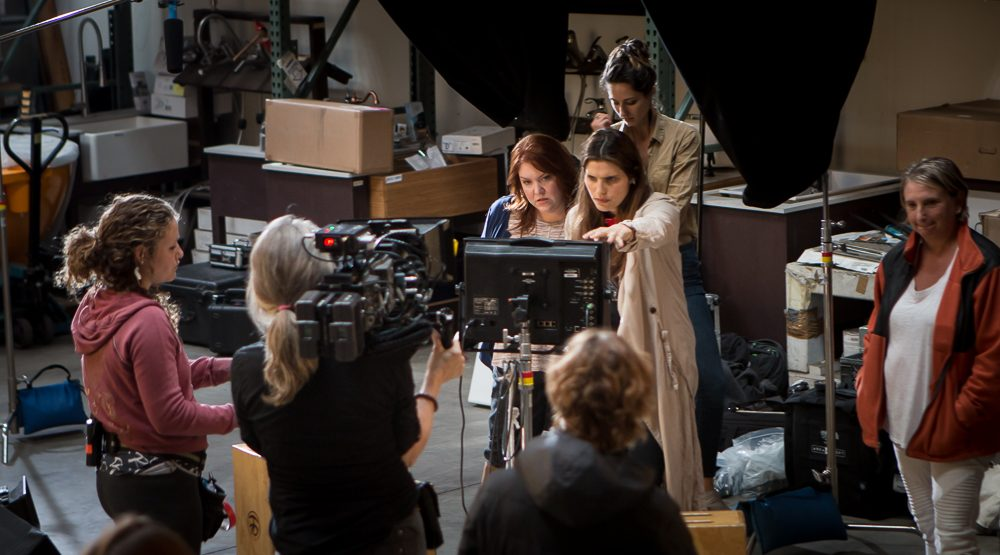 Seven women crew members, some holding camera equipment, gather around a monitor screen on a film set.