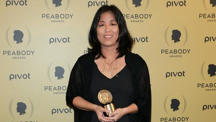 A woman holds her Peabody Award in front of a red carpet backdrop.