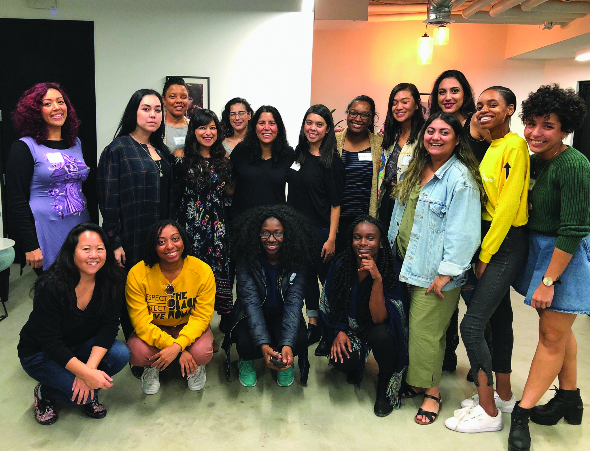 Seventeen young women of color smile in a posed group photo.
