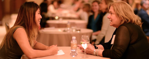 Two women chat, seated across a table from each other.