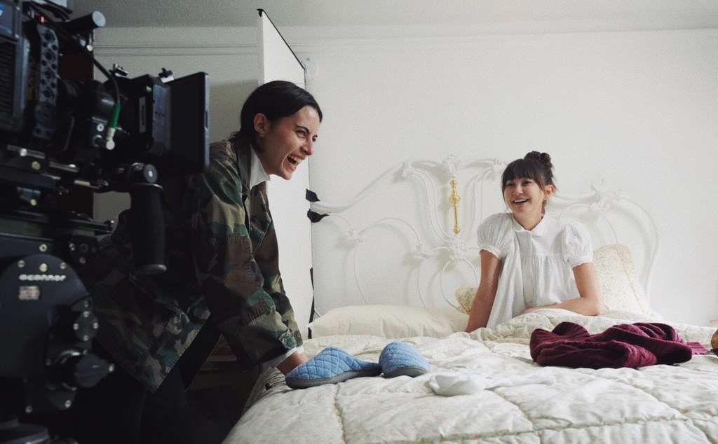 A camera in the foreground is aimed at two laughing women, a filmmaker and her actor.