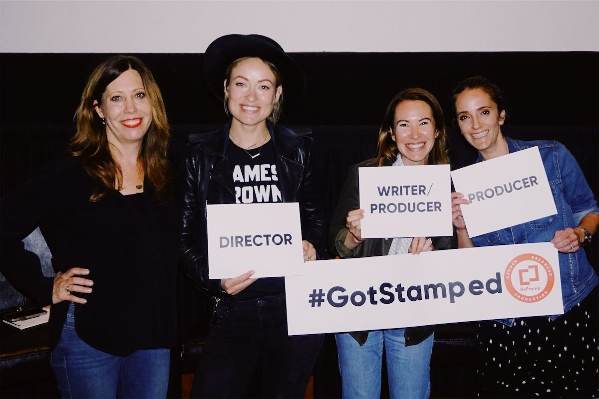Four women smile in front of a theater screen holding signs with their crew titles on them.