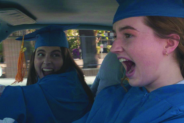 Girls in graduation caps and gowns scream with joy while driving in a car.