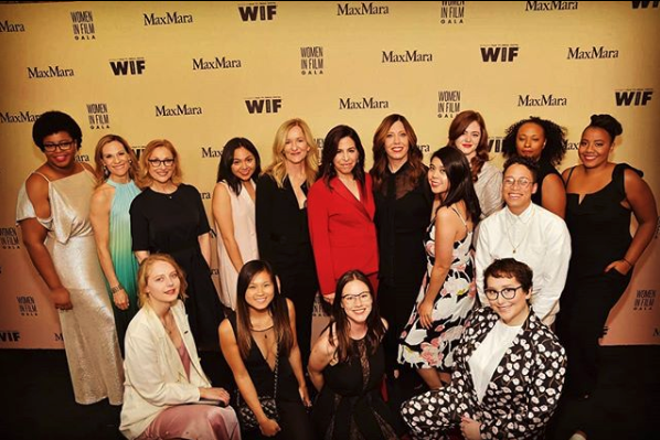 Sixteen sharply dressed women pose in front of a photo backdrop on a red carpet.